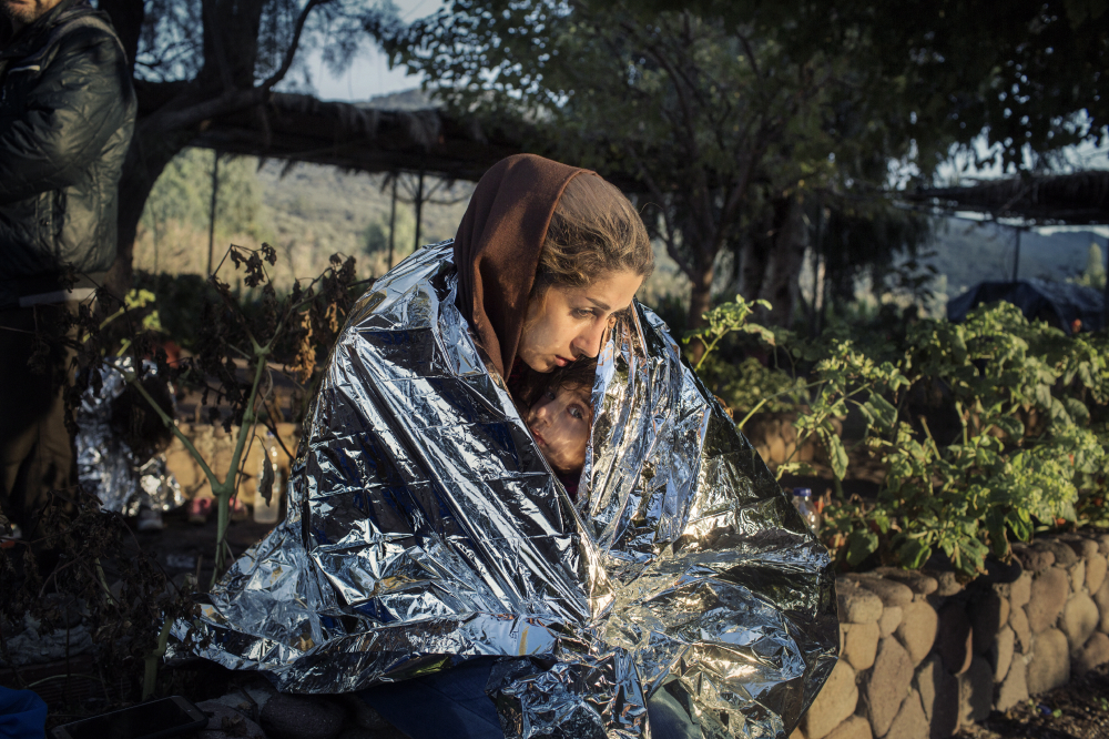 Lesvos, Greece Oct. 18, 2015. A mother and child  wrapped in an emergency blanket after disembarking on the beach of Kayia, on the north of the Greek island of Lesvos.