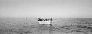 2015. Lesvos. Greece. A wooden boat carryng Syrians, including women and children, approaches the  shore near Molyvos on the Greek island of Lesvos.