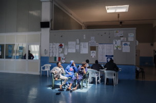 2015. Pozzallo. Sicily, Italy.  Young asylum seekers sit in the sun coming through the skylights of the CPSA (Centro di primo soccorso ed accoglienza – first reception centre) in Pozzallo. While they wait for their position as asylum seekers to be ascertained, they must stay inside this room, and they miss the open space. MSF operates inside the CPSA in Pozzallo, responding to the medical and humanitarian needs of migrants, refugees and asylum seekers.